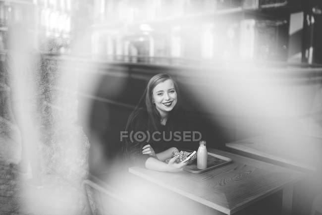 Retrato de menina sorridente com sentado na mesa de café com smartphone e olhando para a câmera — Fotografia de Stock