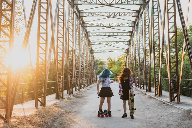 Girls standing on bridge with skateboards — Stock Photo