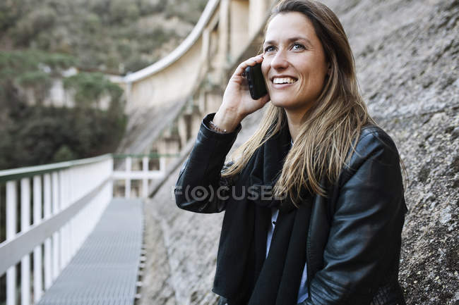 Trendy woman in black leather jacket talking on phone at urban scene — Stock Photo