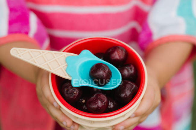 Close-up of little girl holding bowl of fresh cherries with plastic spoon — Stock Photo