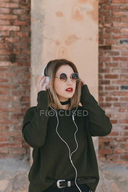 Girl in sunglasses adjusting headphones — Stock Photo