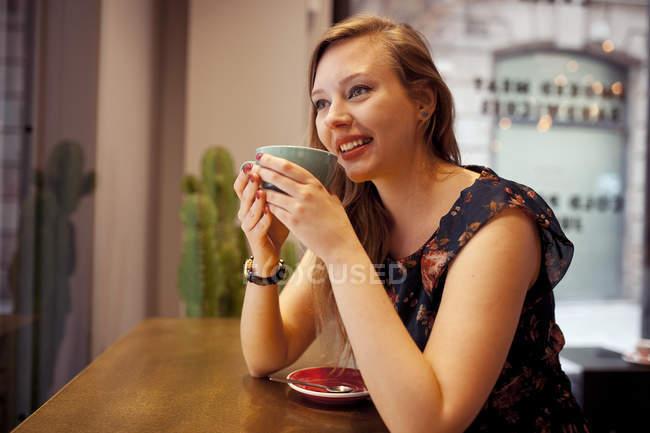 Mulher tomando café sozinha na cafetaria — Fotografia de Stock