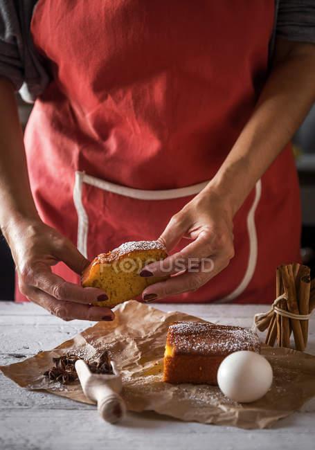 Partie médiane de la tranche femelle tenant du gâteau fait maison sur du papier de boulangerie avec une cuillère d'étoiles d'anis, du gâteau et des œufs sur une table de cuisine rustique blanche — Photo de stock