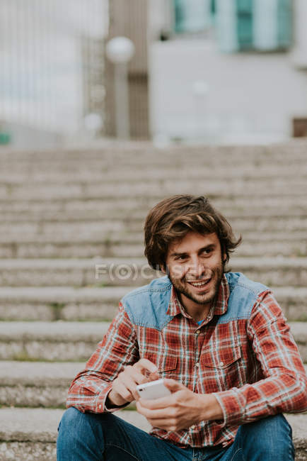 Retrato de homem sorridente em camisa quadriculada sentado em degraus de rua e usando smartphone — Fotografia de Stock