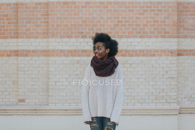 Porträt der jungen Frau posiert in Freizeitkleidung und wegsehen auf Hintergrund der Ziegelmauer — Stockfoto