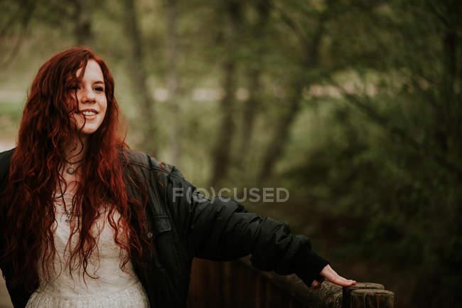 Fröhliches Ingwer Mädchen posiert mit ausgestreckten Händen am Wald — Stockfoto