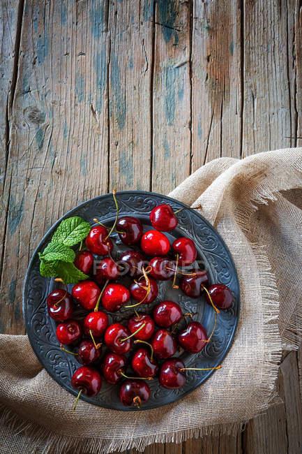 Прямо над зору стиглі вишні в миску на сільському стилі таблиці — стокове фото