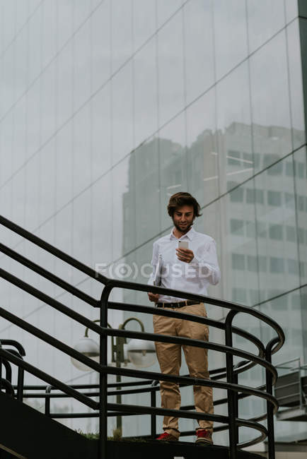 Portrait of smiling businessman in white shirt standing on stairs passage and using smartphone  over business building glass facade on background — Stock Photo