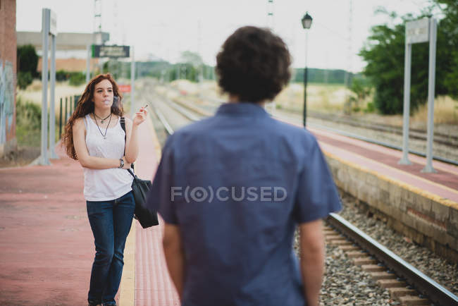 Rear view of man looking at smoking girl with curvy red hair on railway platform — Stock Photo