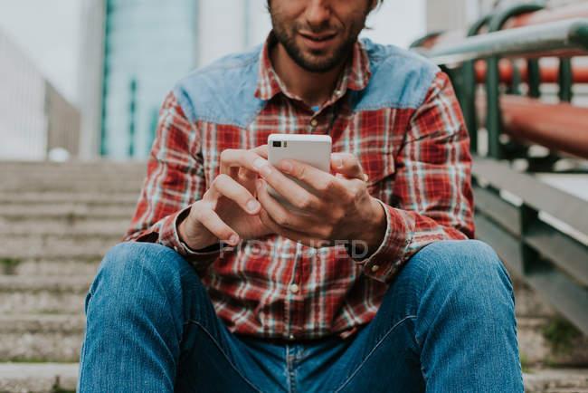 Hombre de la cosecha en el teléfono inteligente de navegación camisa comprobada mientras está sentado en los pasos - foto de stock