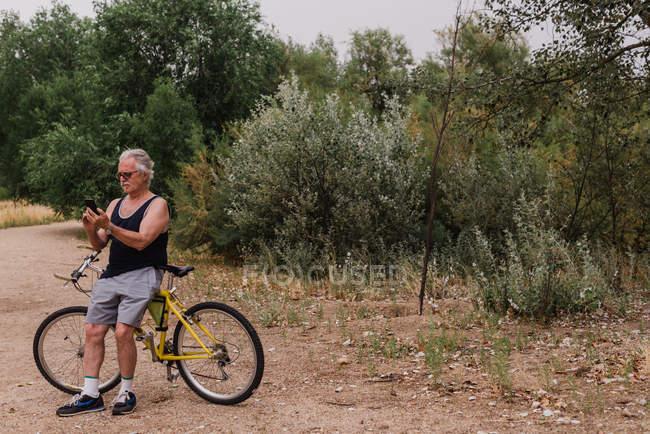 Portrait d'un homme âgé appuyé sur le vélo et le smartphone de navigation dans le parc — Photo de stock