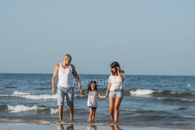 Portrait de famille marchant sur la plage et se tenant la main . — Photo de stock
