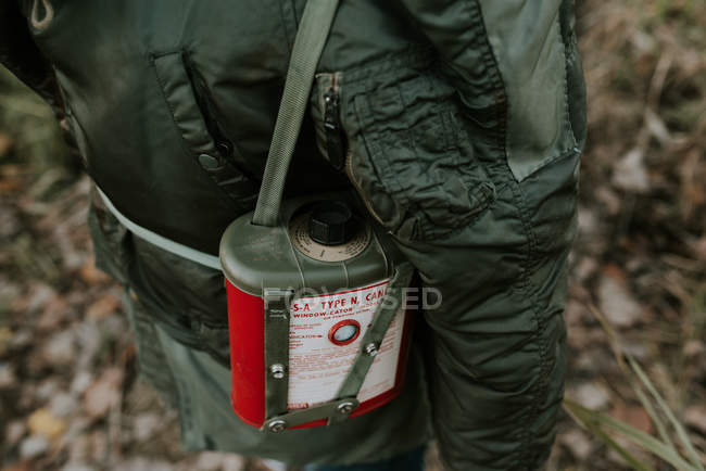Cropped image of person carrying gas mask filter flask on shoulder — Stock Photo