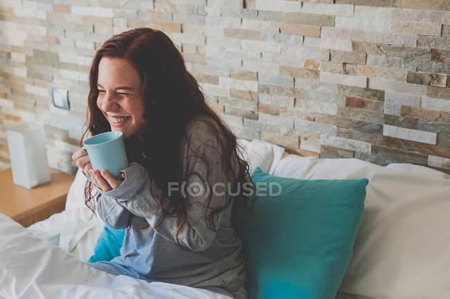 Ragazza seduta a letto e tenendo la tazza blu — Foto stock
