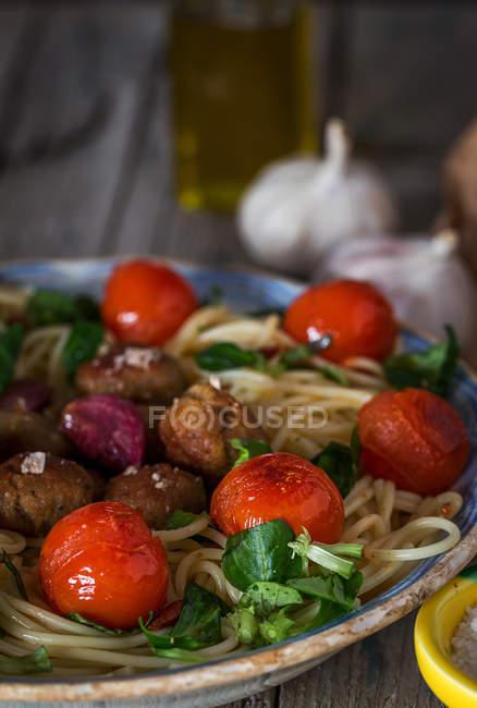 Spaghetti und Fleischbällchen garniert mit Basilikum und gegrillten Tomaten auf Teller — Stockfoto