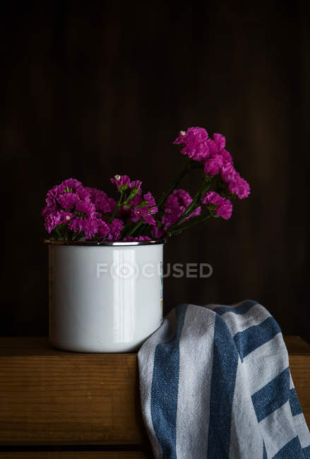 Still life of purple flowers in white mug on table with towel — Stock Photo