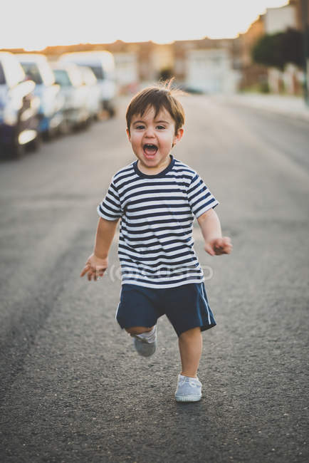 Portrait of cute boy in shorts running happily towards camera on road. — Stock Photo