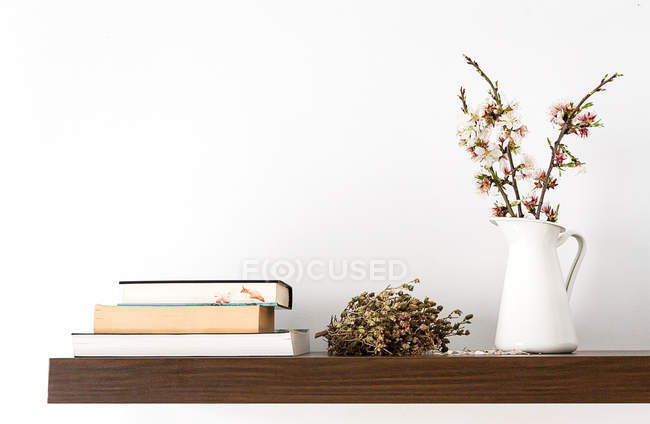 Fresh cut blooming sprigs in vase on shelf with books — Stock Photo