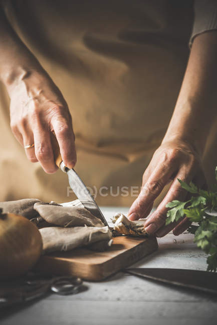 Close up of female slicing pleurotus mushrooms on wooden board with knife — Stock Photo