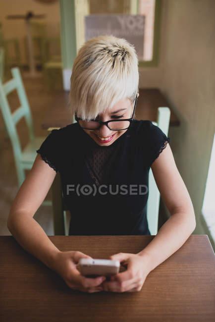 Girl using smartphone in cafe — Stock Photo