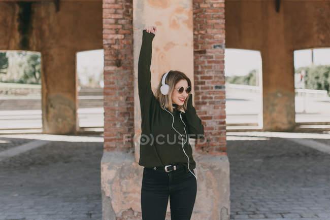 Fille dans les écouteurs posant avec leva les bras — Photo de stock