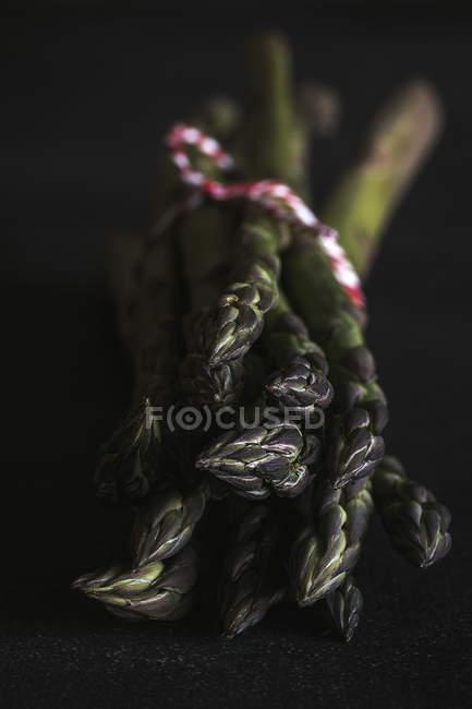Frischer grüner Spargel auf schwarz — Stockfoto
