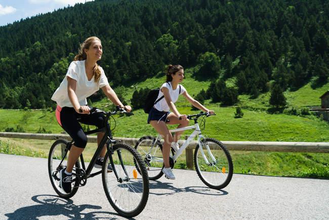 Girls riding bikes on mountain road — Stock Photo