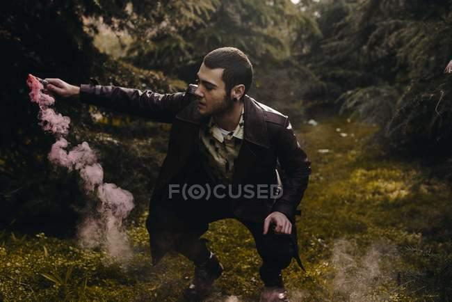 Retrato de hombre con estilo con vela de humo rosa en la mano en cuclillas entre los bosques - foto de stock