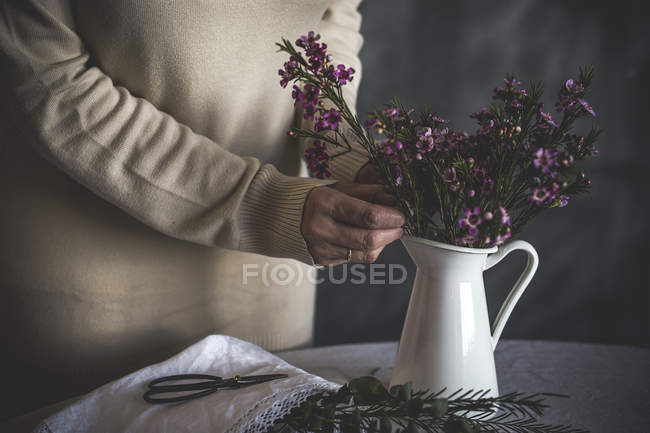 Mid section of female florist placing flower in vase on table — Stock Photo