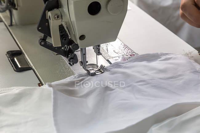 Close-up vista da máquina de costura com tecido branco — Fotografia de Stock