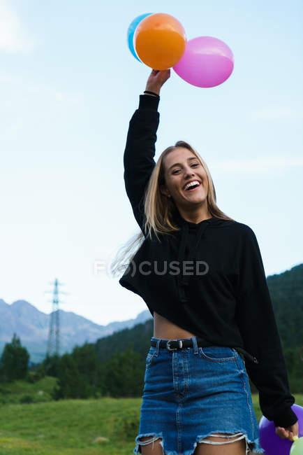 Усміхаючись білявка позують з повітряних куль на природі — стокове фото