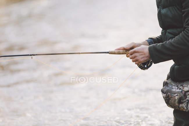 Milieu de l'homme pêche avec canne sur la rivière — Photo de stock
