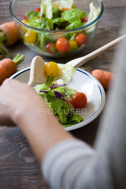 Crop hands mixing salad in plate — Stock Photo