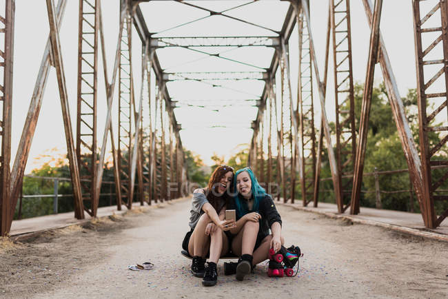 Two teen girls sitting on skateboard and making selfie. — Stock Photo