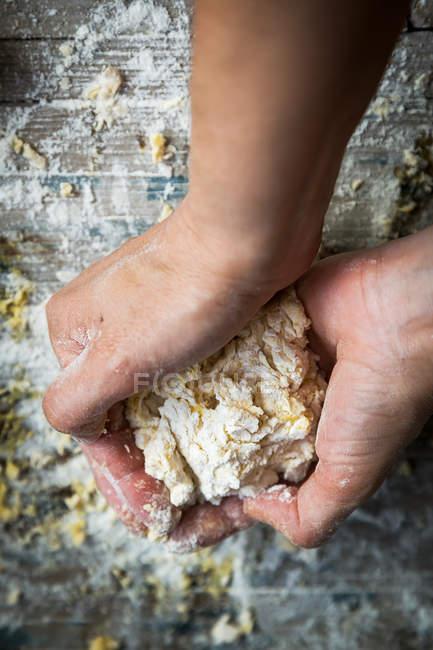 Au-dessus des mains pétrissant la pâte sur la table rurale en bois — Photo de stock
