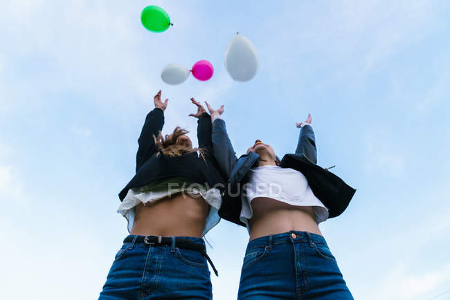 Bottom view of women throwing up balloons — Stock Photo