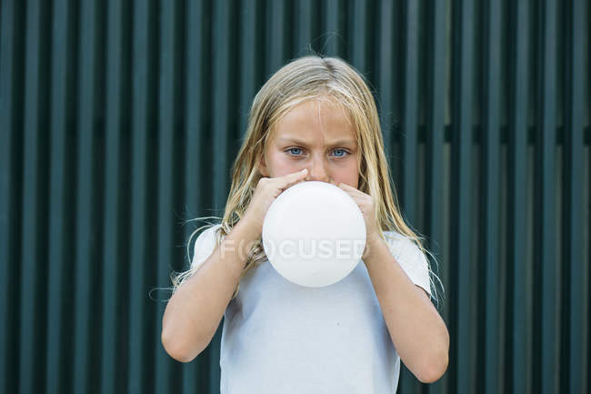 Portrait of serious little girl looking at camera while blowing white balloon at street. — Stock Photo