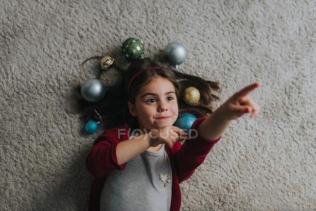 Над видом девушки, лежащей на ковре с рождественскими безделушками вокруг головы и указывающей пальцем — стоковое фото