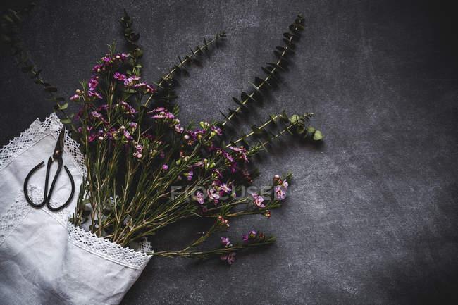 Vista piatta del mazzo di fiori avvolto in tovagliolo bianco con le forbici sulla superficie di pietra — Foto stock