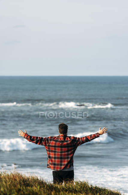 Rear view of man standing with outstretched hands on seashore — Stock Photo