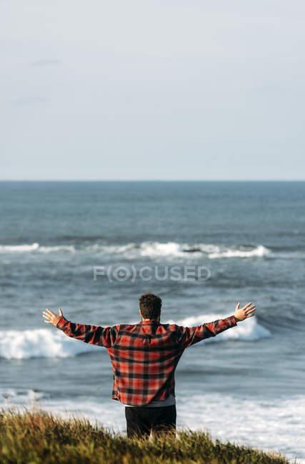 Vue arrière de l'homme debout, les mains tendues au bord de mer — Photo de stock