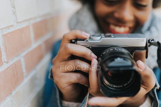 Bouchent la vue de la jeune fille souriante prendre photo avec caméra analogique — Photo de stock