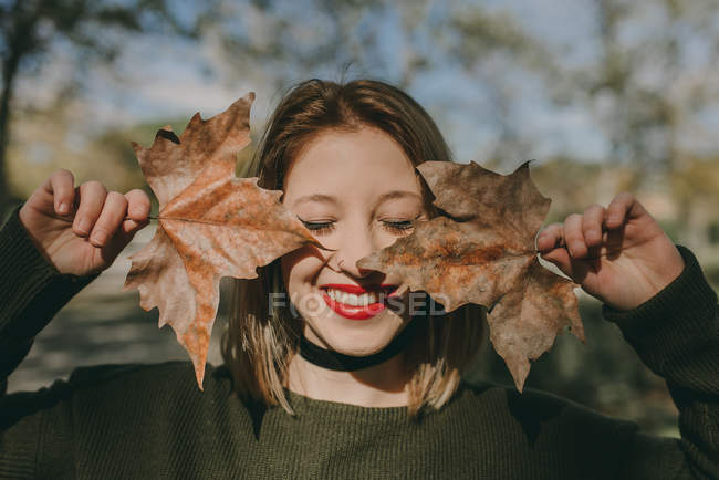 Girl with eyes closed holding maple leaves near face — Stock Photo