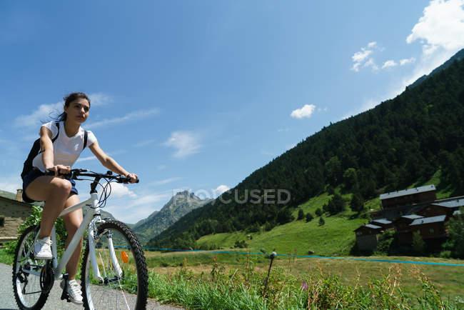 Menina andar de bicicleta na estrada rural — Fotografia de Stock