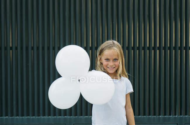 Ragazza sorridente alla macchina fotografica mentre tiene tre palloncini bianchi — Foto stock