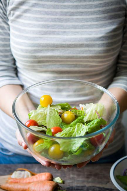 Животик женщина, держа тарелку с салатом — стоковое фото