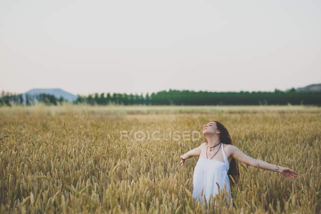 Портрет беззаботной рыжеволосой девушки позирует с протянутыми руками и закрытыми глазами на ржаном поле — стоковое фото
