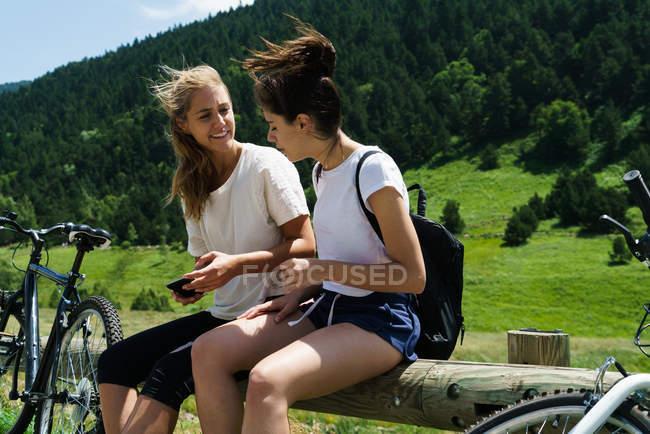 Mädchen sitzen mit Fahrrädern und mit smartphone — Stockfoto