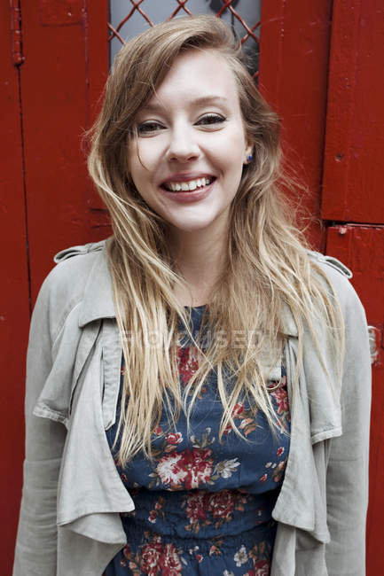 Lächelnde junge Frau blickt in die Kamera über roter Tür auf Hintergrund — Stockfoto