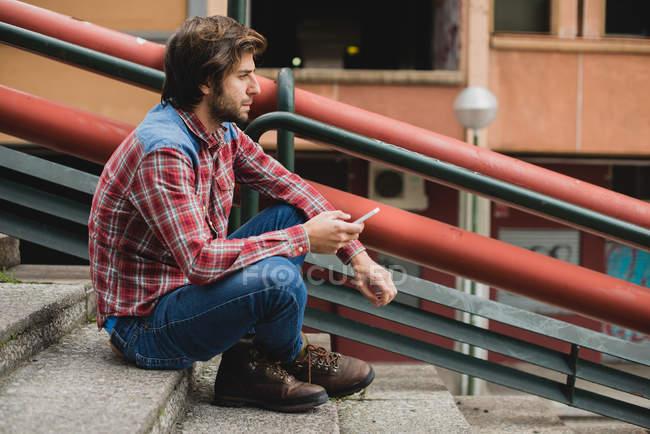 Vista lateral del hombre barbudo con ropa casual sentado en las escaleras de la calle con teléfono inteligente y mirando hacia otro lado - foto de stock